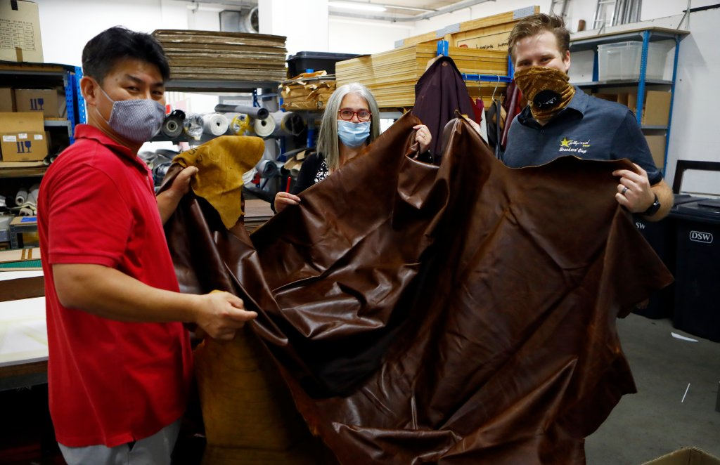 Hollywoodbet's Devin Heffer and Nanuja's KwangJeon and Natasha Lee holding genuine leather hide